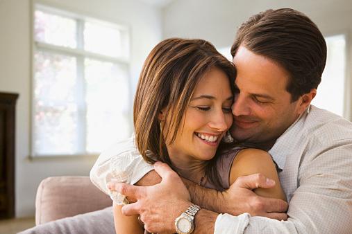 Couple hugging and smiling at home